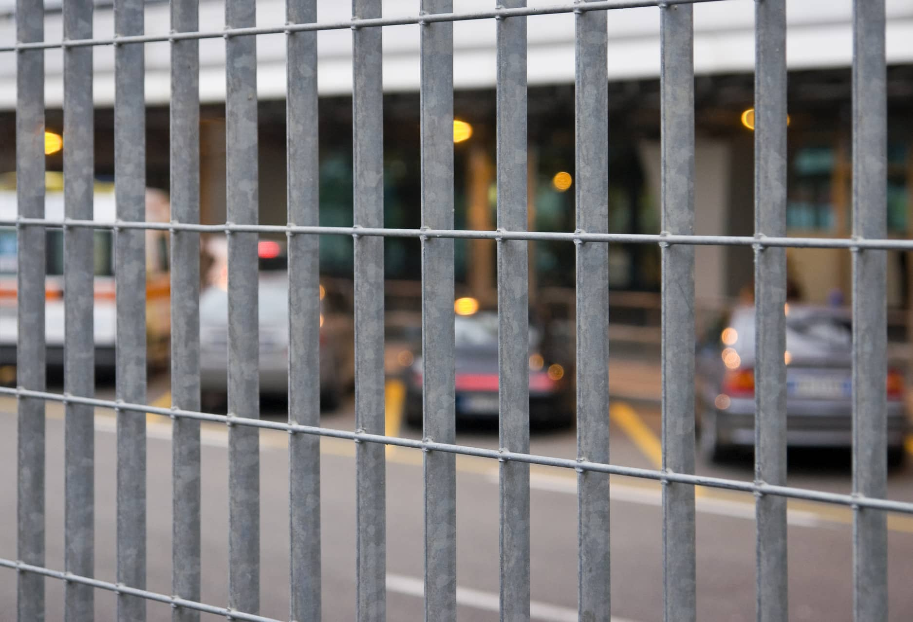 This picture shows a metal fence surrounding a commercial parking lot area.