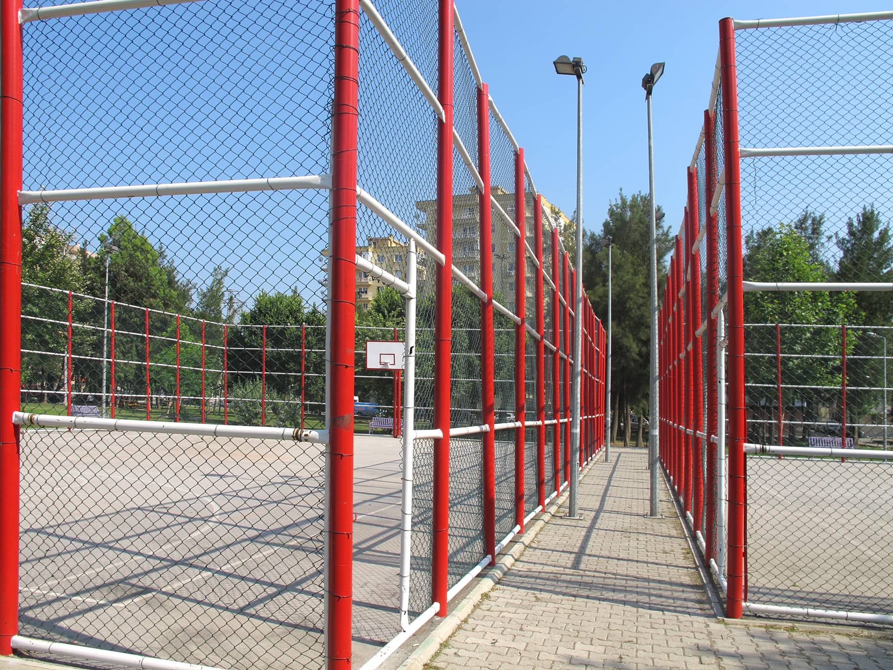 An image of metal fencing surrounding a basket ball court.