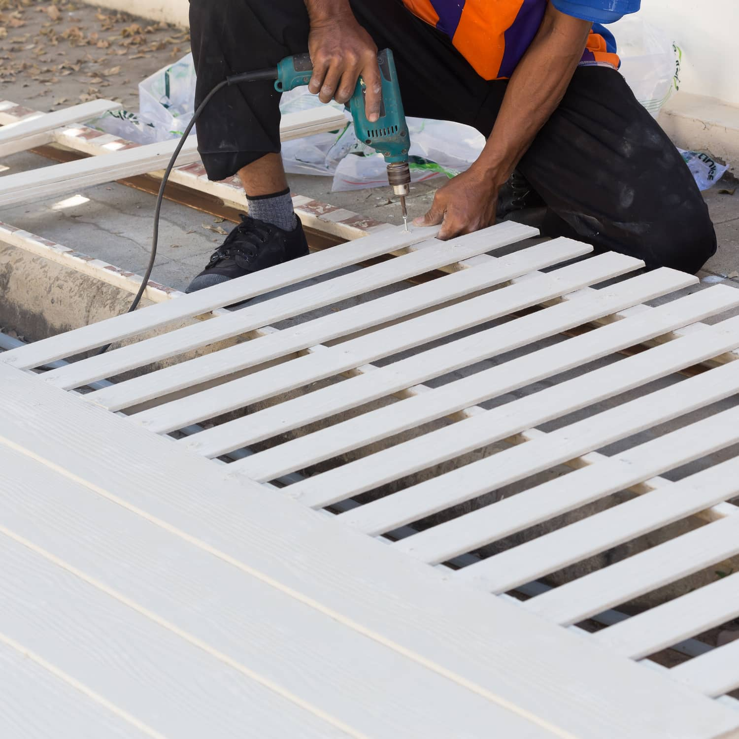 Image of a contractor putting together a white fence.