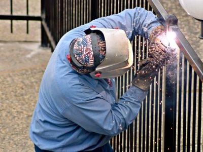 This image shows a metal fence fabricator performing welding to a black metal fence.