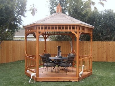 A gazebo in a back yard with table and chairs.